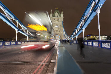 Great Britain, England, London, View of Double-Decker Bus, blurred on tower bridge at night - WDF000837