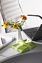 Office scene with flower vase, gift parcel and laptop on desktop - CSF014059