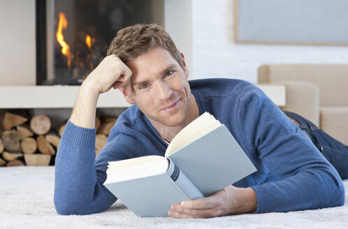 Germany, Munich, Mid adult man reading book at home, portrait - NHF001325