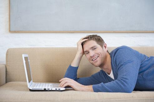 Germany, Munich, Mid adult man using laptop, smiling, portrait - NHF001322