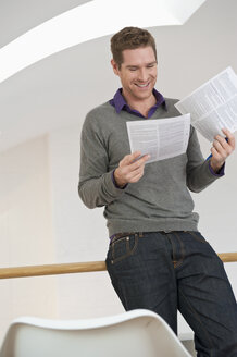 Germany, Bavaria, Munich, Mid adult man with document, smiling - NHF001321