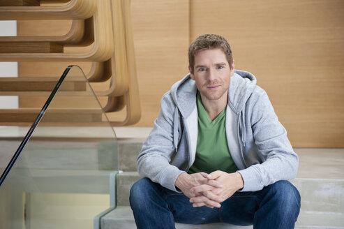 Germany, Munich, Mid adult man sitting on steps, portrait - NHF001317