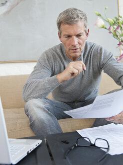 Germany, Munich, Mature man doing paperwork with laptop - NHF001300