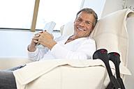 Germany, Munich, Mature man sitting on chair, smiling, portrait - NHF001328