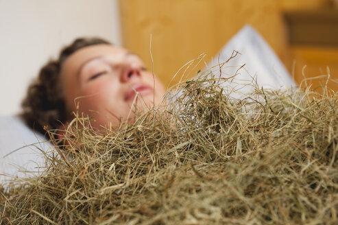 Italy, South Tyrol, Woman having hay bath in hotel urthaler - WESTF015801