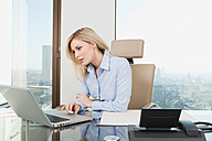 Germany, Frankfurt, Business woman using laptop in the office - SKF000425