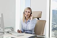Germany, Frankfurt, Business woman wearing headset, smiling, portrait - SKF000437