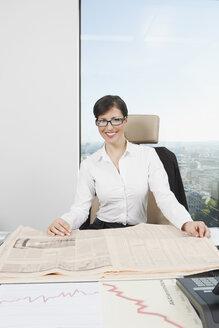 Germany, Frankfurt, Business woman with newspaper - SKF000458