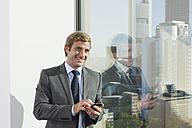 Germany, Frankfurt, Businessman using phone in office, smiling, portrait - SKF000467