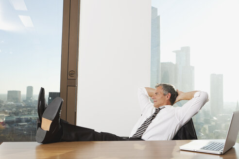 Germany, Frankfurt, Businessman resting in office with laptop on table - SKF000491
