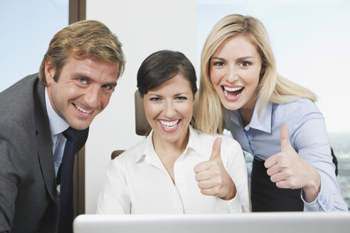 Germany, Frankfurt, Business people using laptop and showing thumbs up - SKF000524