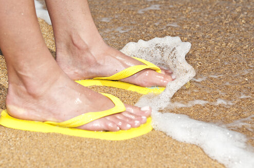 Woman with flip flops in waves, close up - UMF000343