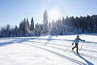 Germany, Bavaria, Isar Valley, Senior woman doing cross country skiing - MIRF000091