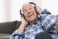 Germany, Wakendorf, Senior man wearing head phones, smiling - WESTF016214