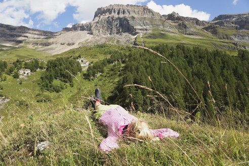 Switzerland, Valais, Mature woman resting in grass - GWF001401