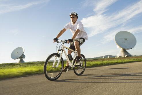 Germany, Bavaria, Raisting, Man riding electric bicycle near radio station - RNF000661