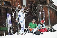 Austria, Kleinwalsertal, Friends sitting by mountain hut - MRF001235