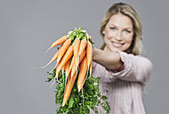 Mid adult woman holding bunch of carrots, portrait - WESTF016265