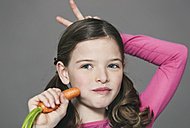 Girl eating carrot, close up - WESTF016283