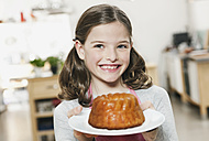 Germany, Cologne, Girl holding cake in a plate, portrait - WESTF016289