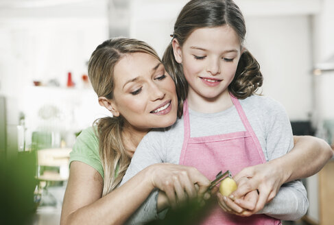 Germany, Cologne, Mother and daughter peeling potato - WESTF016301