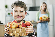 Germany, Cologne, Boy holding apple basket with mother in background - WESTF016310