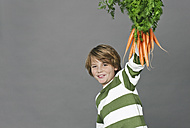 Boy holding a bunch of carrots, portrait - WESTF016331