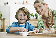 Germany, Cologne, Mother and son cutting bread in kitchen - WESTF016337