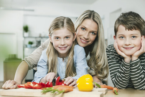 Germany, Cologne, Mother and children cutting vegetables in kitchen - WESTF016352