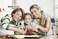 Germany, Cologne, Mother and children making pizza in kitchen - WESTF016364