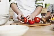 Germany, Cologne, Boy cutting vegetables - WESTF016376