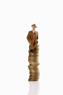 figurine man with hat sitting on coin stack - CSF014719