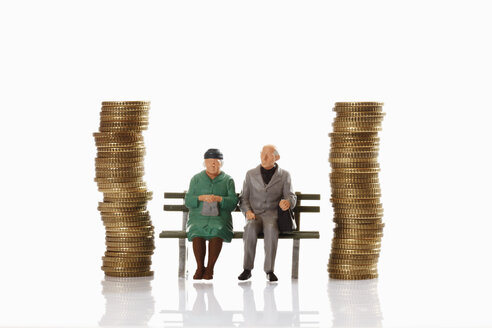 Figurines of old age pensioner sitting on bench between coin stacks - CSF014722