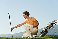 Italy, Kastelruth, Mid adult woman holding golf club on golf course - WESTF016479
