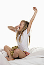 Girl sitting on bed and yawning - WWF001871