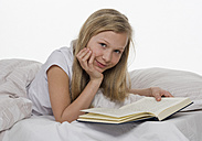 Girl lying on bed with book, portrait - WWF001875