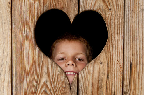 Austria, Salzburger Land, Alpine Pasture, Boy peeking from wooden door - UMF000351