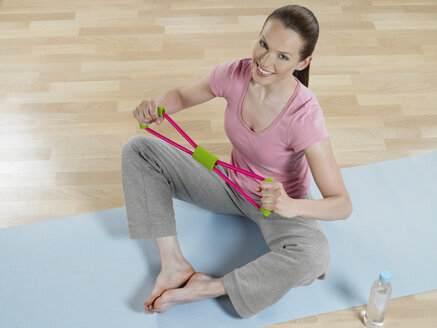 Young woman doing exercise, smiling, portrait - JLF000323