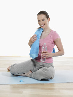 Young woman relaxing after yoga, smiling - JLF000326