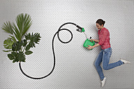Mid adult woman filling fuel in petrol can with hose through plants - BAEF000217
