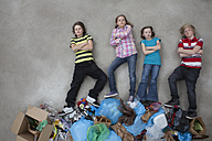 Children on stack of garbage and showing ecology symbol - BAEF000271