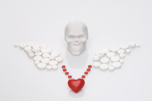Skull, pills and drugs forming medical symbol on white background - ASF004306