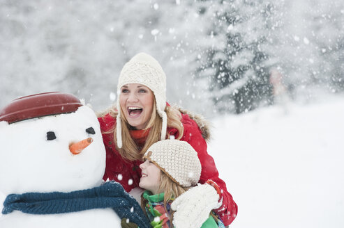 Austria, Salzburg, Hüttau, Mother and daughter with snowman, smiling - HHF003613