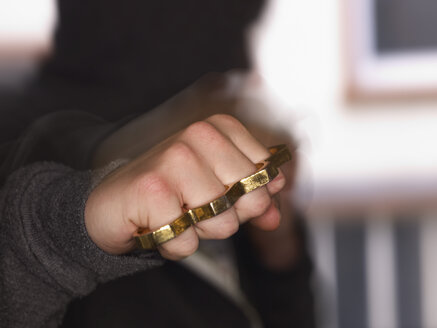 Young man showing fist with brass knuckles - AKF000333