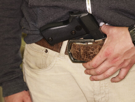 Young man with gun in belt - AKF000239