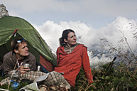 Austria, Salzburg, Filzmoos, Couple sitting beside tent on mountain and looking at view - HHF003546