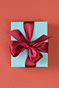 Gift box tied with red ribbon on red background - ASF004321