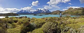 South America, Chile, Patagonia, Torres del Paine National Park, Cuernos del Paine from Lake Pehoe, female photographer standing beside lake - FOF003194