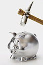 Silver piggy bank with hammer on top of it against white background, close up - WBF001023