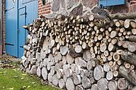 Germany, Kratzeburg, Stack of firewood near country house - WESTF016582
